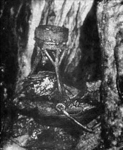 """Il tripode ancora posto nel così detto """"altare"""", assieme ad altri oggetti cultuali."""